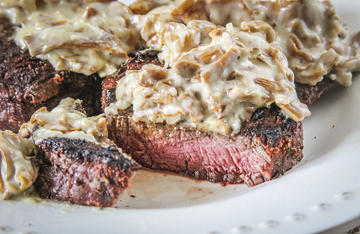 Creamy, cheesy chanterelle mushroom sauce over grilled elk backstrap.