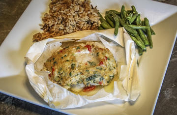 Crappie fillets topped with crabmeat stuffing and baked in a parchment packet make the perfect summertime dinner.