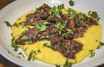 Serve the tender braised shanks over a bed of creamy cheese grits and topped with the flavorful gravy from the pot.