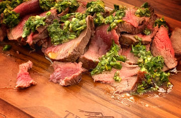 Brush away the salt, slice the backstrap, then top with chimichurri sauce.