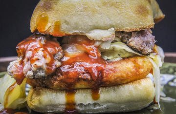 Tender roasted cabbage, a crunchy fried potato cake, split and pan-fried venison brats and spicy BBQ sauce combine to turn this classic British dish into a sandwich.