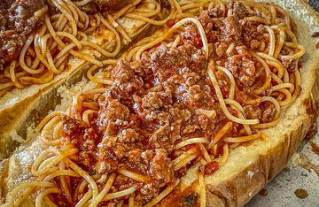 Pile spaghetti with venison sauce between buttered garlic bread slices for a sandwich that will feed a crowd.