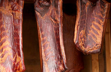 Cold smoking gives the bacon a rich mahogany color and spectacular flavor.