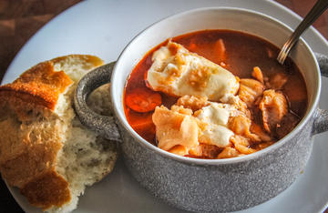 A bowl of fish stew and a chunk of crusty bread is a perfect meal on a cool day.