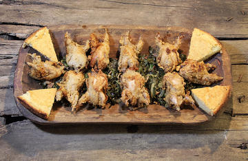 Serve the crispy fried quail over a bed of slow cooked collard greens.
