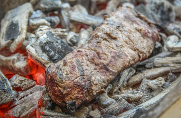 Cooking meat directly on the coals may seem primitive, but the results speak for themselves.