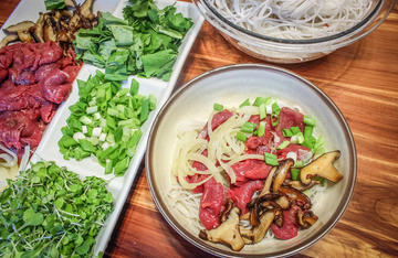 Build your pho bowl and ladle over the boiling bone broth to cook the ingredients.