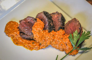 Sliced grilled backstrap served with Spanish Romesco Sauce.
