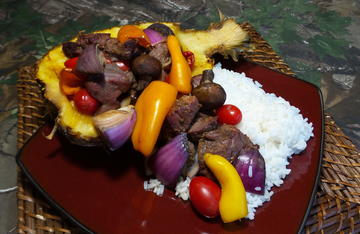 Smoked venison pineapple boats served with white rice.