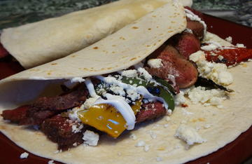 Wrap the meat and vegetables in a warm tortilla and top with crumbled queso fresco and sour cream.