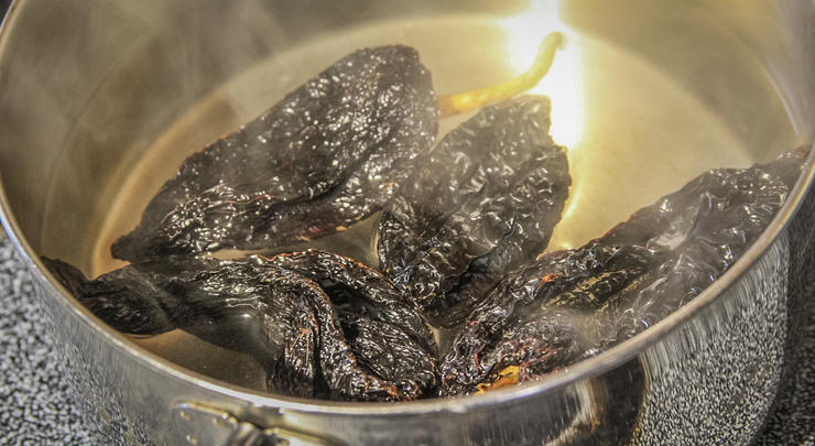 Soak the dried ancho chili peppers in hot water until soft.