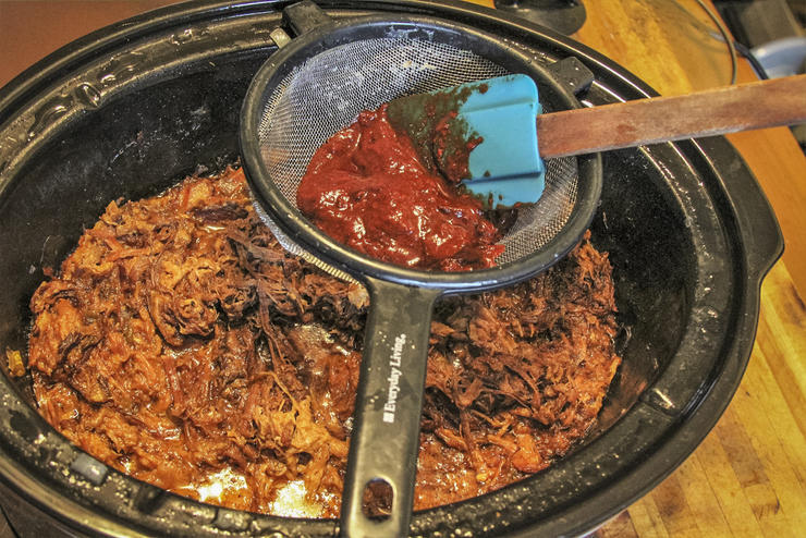 Push the ancho pepper pulp through a wire strainer into the cooked venison and pork.