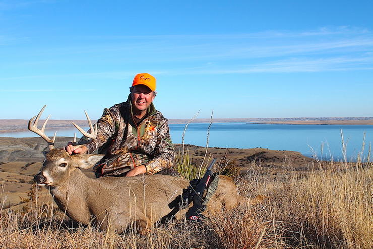 The author poses with a big, mature buck. (Doug Howlett photo)