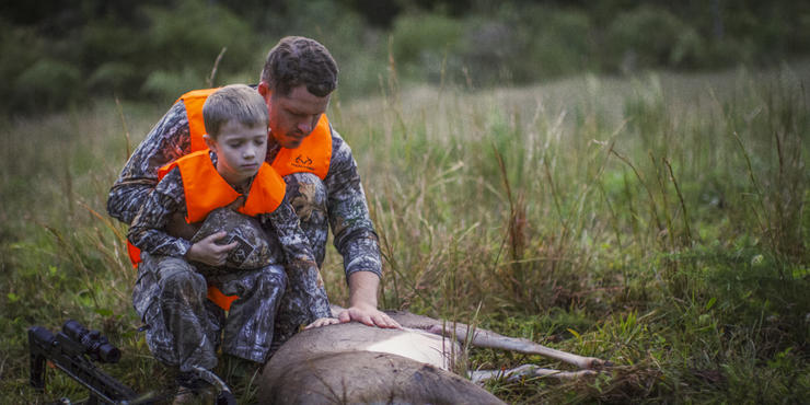 Bancroft and son with a deer from their hunt.