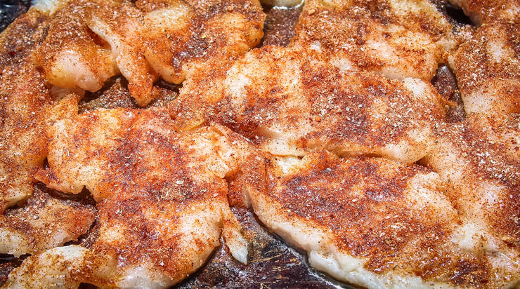 Sprinkle the seasoning evenly over the butter dipped fish.