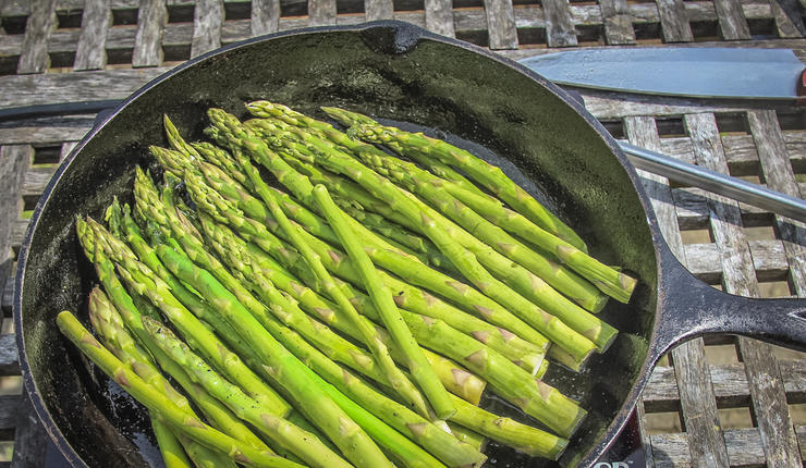 After the bacon cooks, add the asparagus to the skillet and cook for a few minutes to soften.
