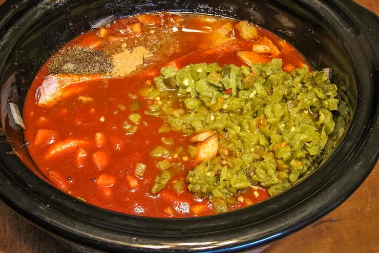 Add the enchilada sauce, peppers, onions, spices and seasonings to the slow cooker.