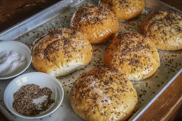 Brush fresh Kaiser rolls with butter, then sprinkle heavily with kosher salt and caraway seeds before baking.