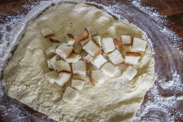 Flatten the dough onto a floured surface and add the dried bread to the center before kneading into a ball.