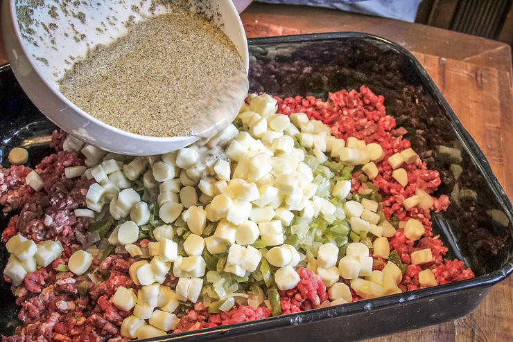 Blend peppers, onions, cheese chunks and seasoned liquid into the meat.