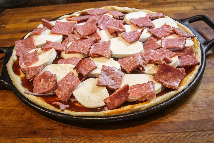 Top the pizza with the onion, bacon, and sliced whole milk mozzarella cheese.
