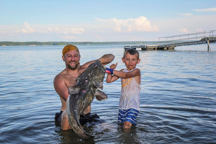 Showing off an average-sized flathead caught by noodling.
