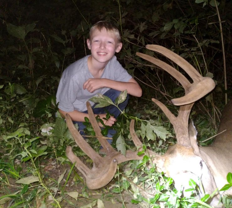 Ashton posing with his dad's buck after the pair tracked and found the deer. Image by Joe Lacefield