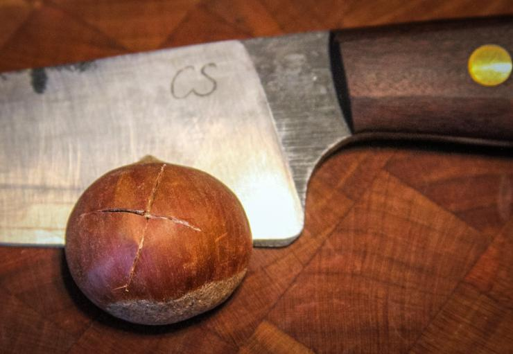 A shallow cross cut with a sharp knife allows steam to escape as the nuts roast.