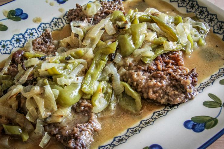 Serve the elk steak topped with the peppers and and onions and lots of gravy.