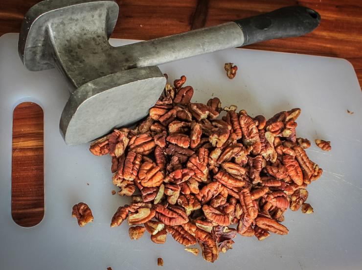 Roughly crush the pecans with a meat mallet.
