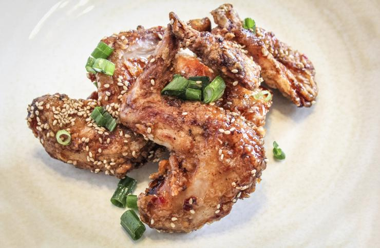 Top the sauced rabbit with the toasted sesame seeds and chopped green onions.