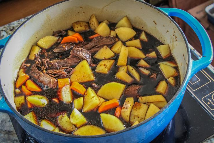 Add the onions, potatoes, peppers, and carrots and simmer until tender.