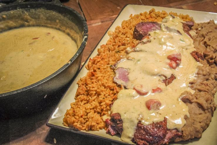 We serve the sliced backstrap with rice and refried beans, then spoon over the smoked queso.
