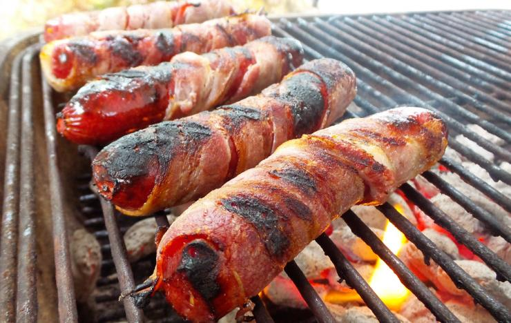Wrap the sausages in bacon and grill until the bacon is crisp and brown.