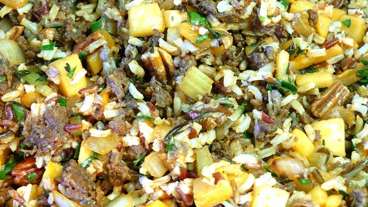 Blend wild rice, diced apples, sausage, pecans and other ingredients to make the stuffing.