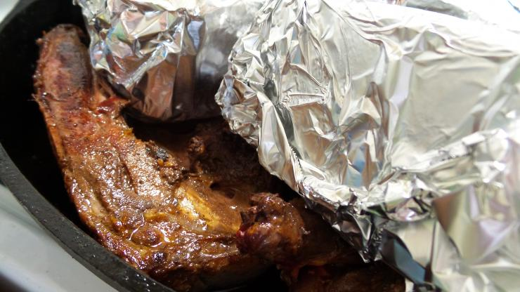 Foil wrapped bricks press the duck's skin tightly against the iron skillet for a perfect sear.