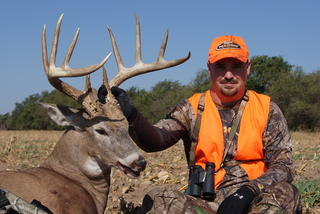 Daniel McVay of Buckventures poses with the buck he shot after crawling out into a field to get in position.