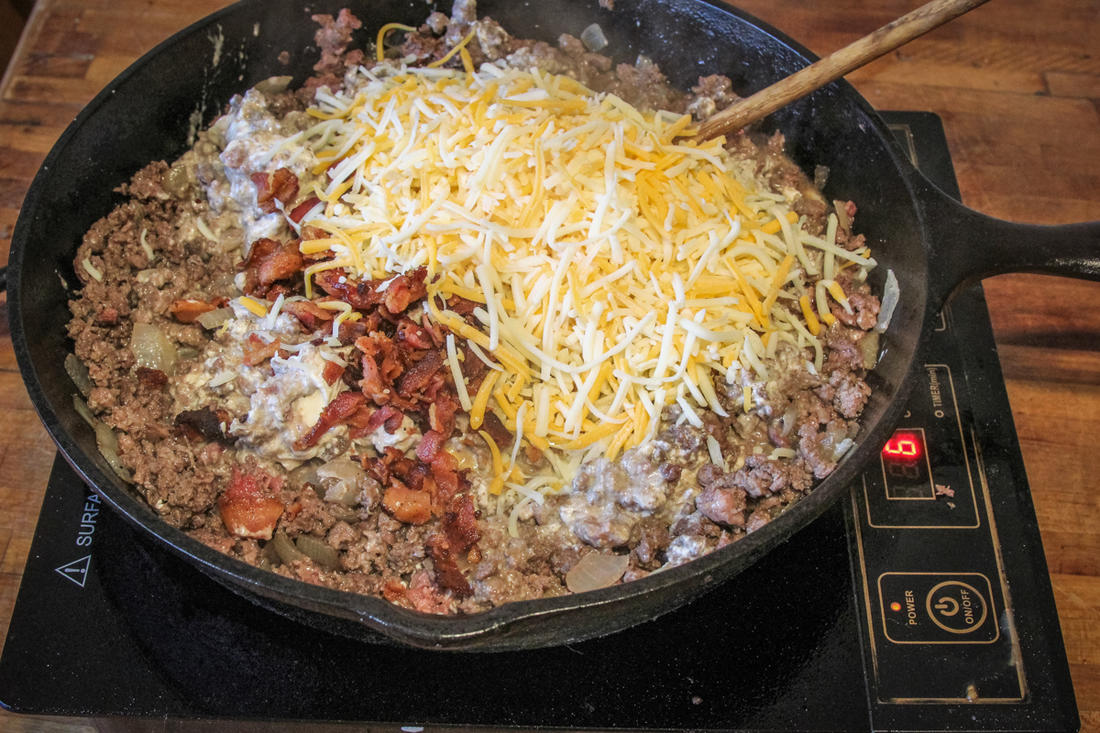 Mix the crumbled bacon, cream cheese and shredded cheese into the browned venison.