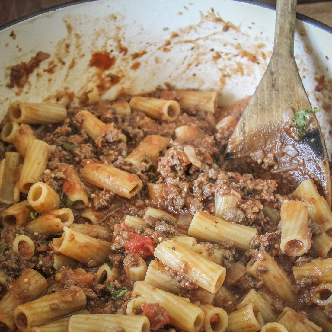 Stir the al dente rigatoni into the meat sauce.