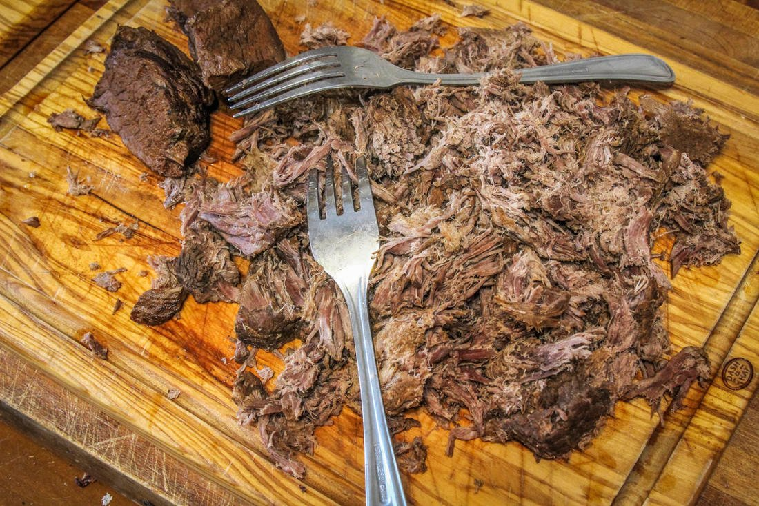 Shred the cooked venison and return it to the slow cooker.