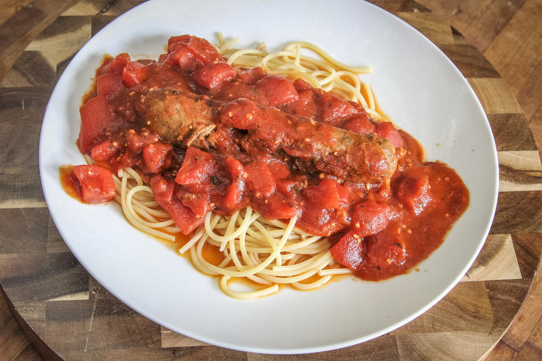 Serve the simmered sausage and sauce over pasta.