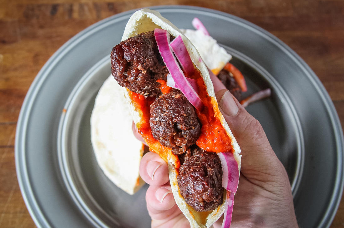 Serve the sausages on pita bread with pickled onions and ajvar spread or roasted bell peppers.