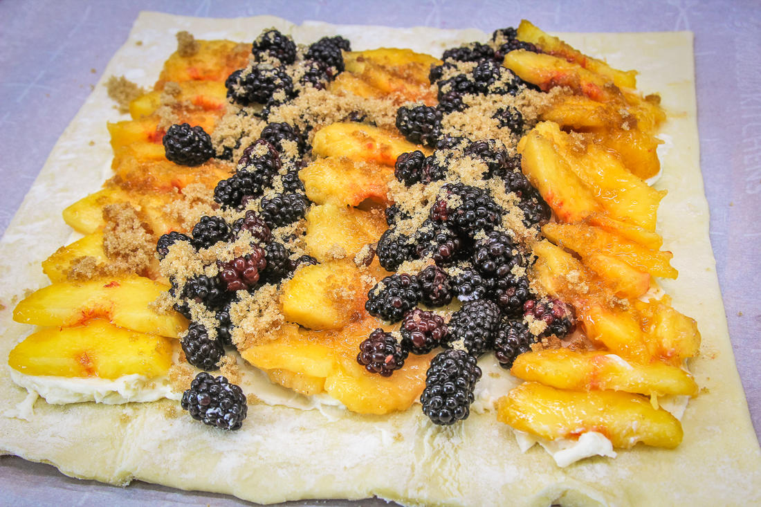 Layer the peaches and blackberries over the cream cheese and top with brown sugar.