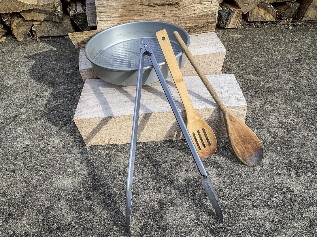Utensils like long metal tongs, wooden spoons and baking pans that fit inside the Dutch oven are handy.