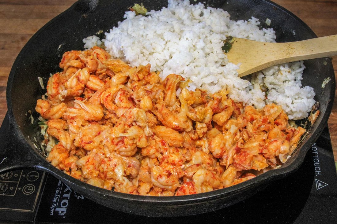 Add the crawfish tails and rice to the pan.