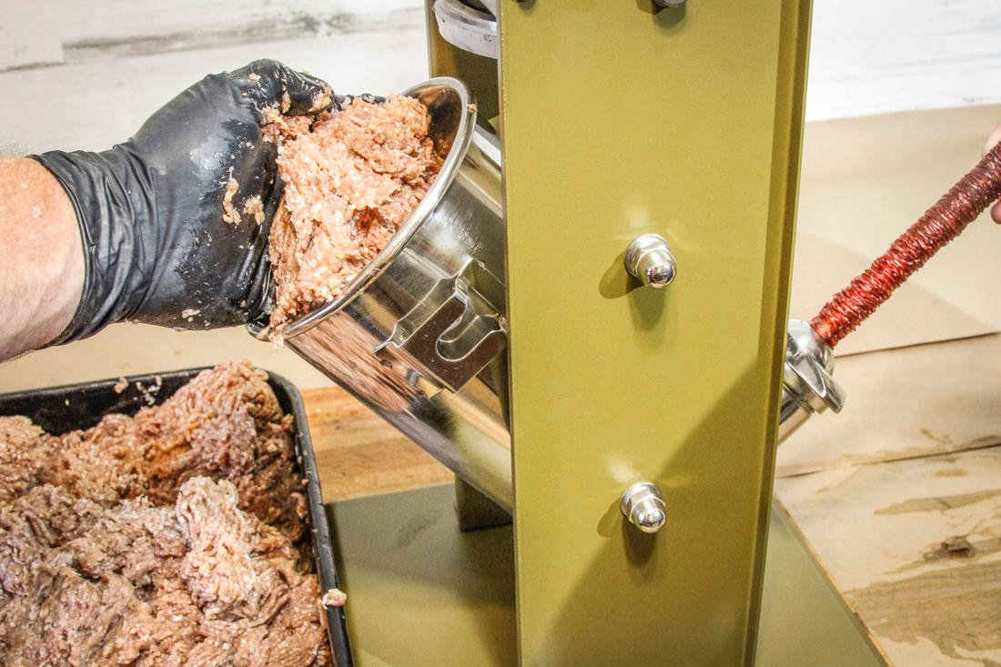 Load the hopper with the seasoned ground meat.