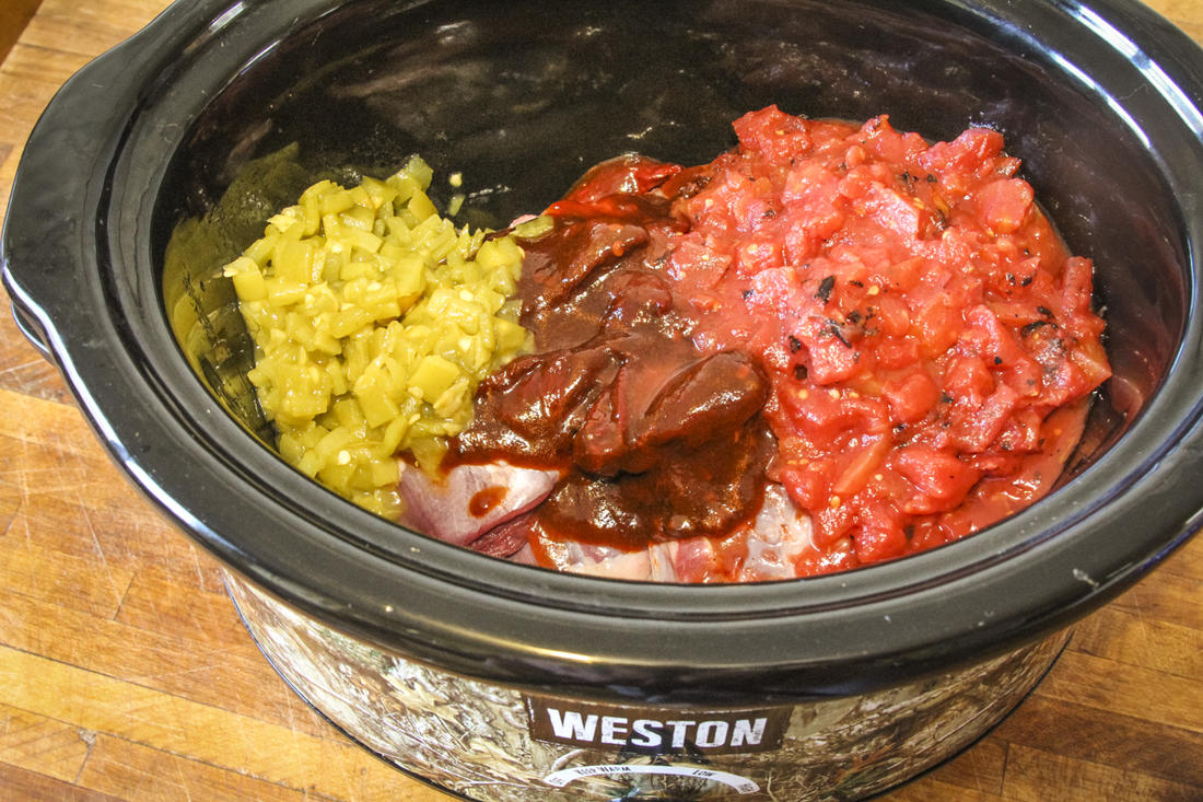 Add the goose, peppers, tomatoes and seasoning to the slow cooker.