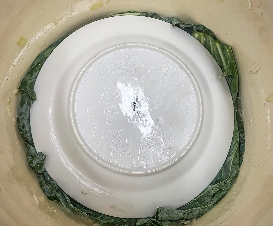 Top the shredded and salted cabbage with a stoneware plate before adding the weights.