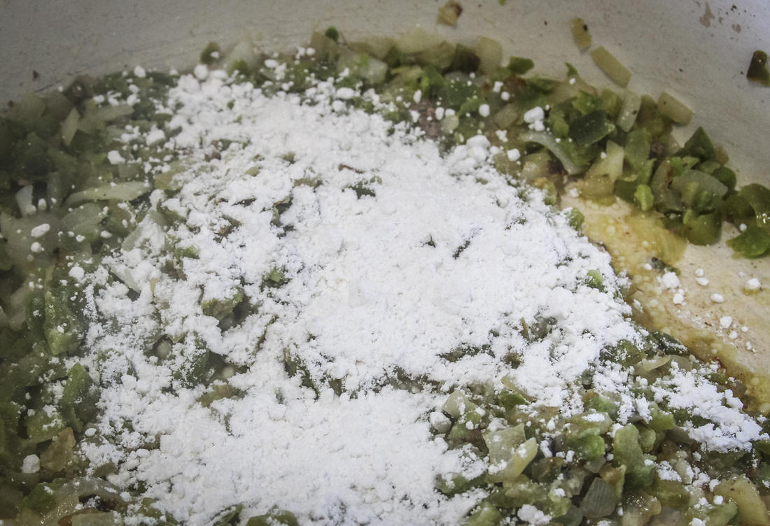 Saute the peppers and onions, then add flour to make a roux.