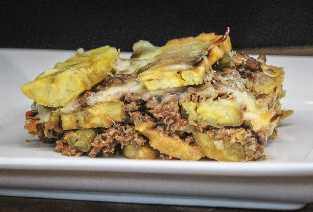 The dish features layers of fried plantain, vegetables, and meaty sauce, all held together by lots of melted cheese.